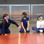 Três crianças estão sentadas no chão. São dois meninos e uma menina. Eles estão vendados a atividade é goalball.