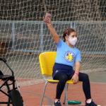 Uma criança aluna do Colégio está sentada em uma cadeira amarela e estão com um saco de areia pequeno em uma das mãos. A atividade é arremesso de peso sentado. A aluna está usando uma camiseta azul clara e máscara de proteção. O cabelo castanho está preso.