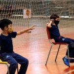 Dois alunos estão sentados em cadeiras e estão com um saco de areia pequeno em uma das mãos. A atividade é arremesso de peso sentado.