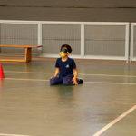Fotografia de um menino sentado no chão da quadra de esportes com uma venda no olho. A atividade é a goalball. O menino está com o uniforem azul marinho do Colégio Miguel de Cervantes.